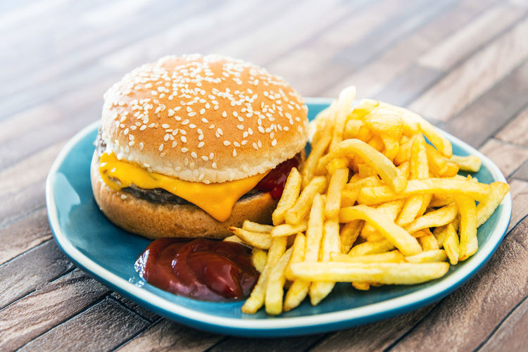 Bun Burger Close-up Fast Food Food Food And Drink French Fries Freshness Fried Hamburger Meat No People Plate Potato Prepared Potato Ready-to-eat Relish Sandwich Snack Still Life Table Take Out Food Temptation Unhealthy Eating Wood - Material