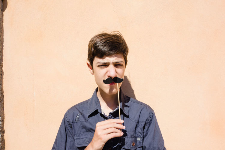 Teenagers posing with party props making funny faces under the sun against a wall Boy Fun Funny Funny Faces Hipster Mediterranean  Moustache Movember Outdoors Paper People Person Sun Sunny Teen Teenager Wall Wall - Building Feature