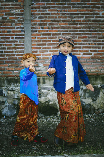 Portrait of cute siblings in traditional clothing against brick wall