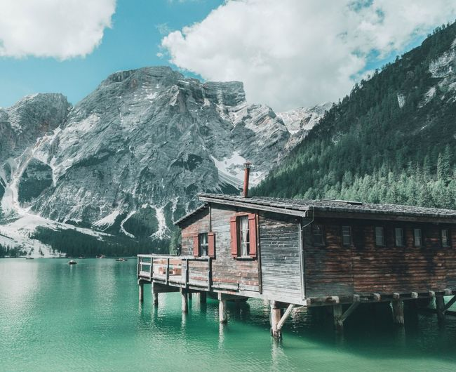 Built structure by lake and mountains against sky