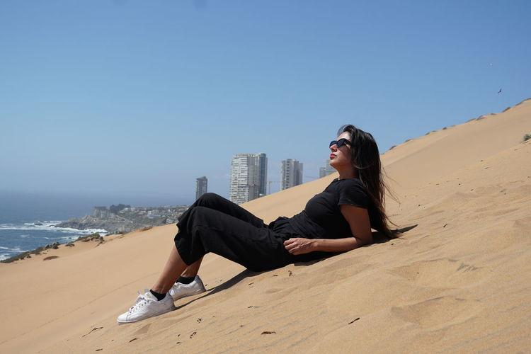 Woman sitting on beach against clear blue sky