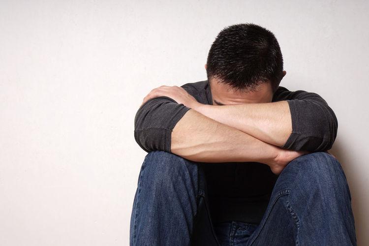 Depressed man sitting against wall