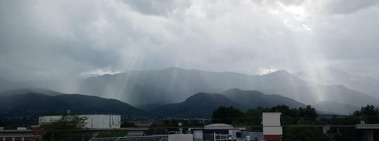 Mountain Range Sun Shining Through Clouds And Rain