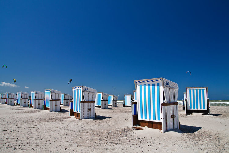 Beach chairs in Warnemuende, Germany. Baltic Sea Beach Blue Calm Clear Sky Closed Copy Space Day Hooded Beach Chair Nature Outdoors Relaxation Sand Sea Shore Summer Sun Lounger Sunlight Sunny Sunshade Tourism Tranquil Scene Vacations Warnemünde Water
