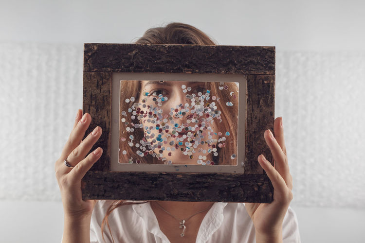 Portrait of woman holding picture frame