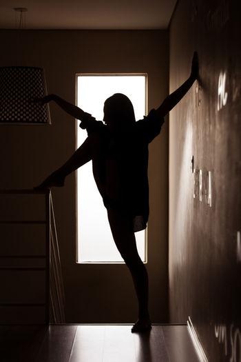 Rear view of woman dancing in corridor
