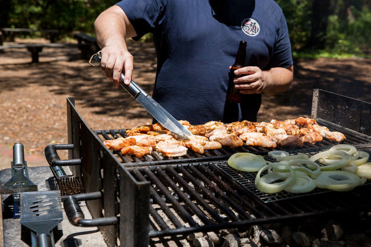Midsection of man cooking food on barbecue