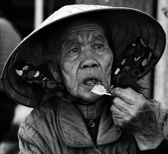 Senior woman looking away while having food outdoors
