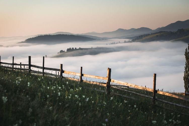 View of wooden railing against cloudscape