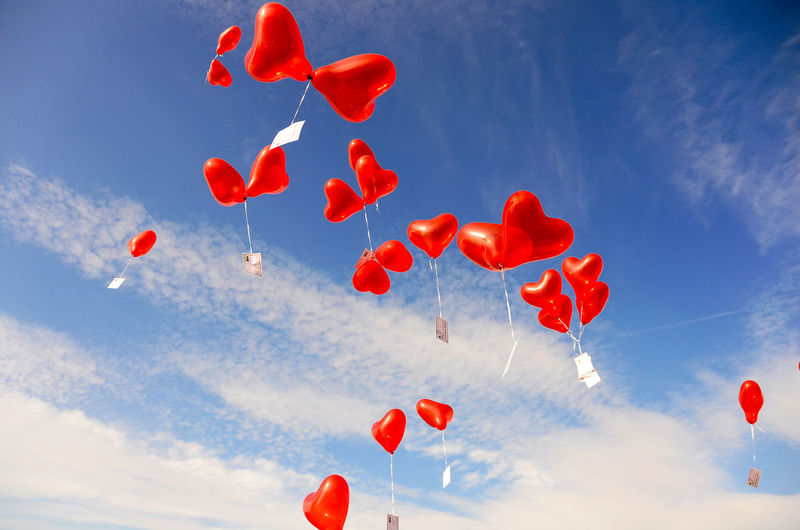 Low angle view of red heart shaped helium balloons flying against sky