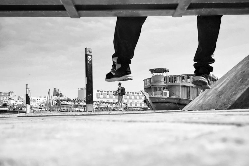 Low section of man standing on bridge against sky in city
