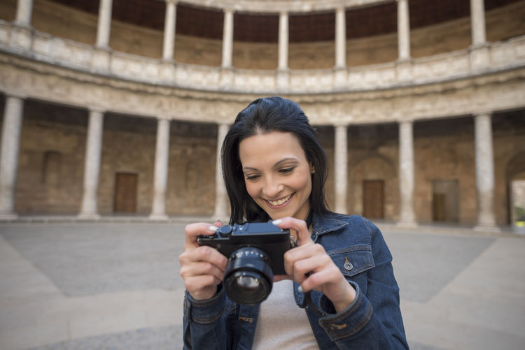 Beautiful smiling young woman looking at camera while standing against ancient building