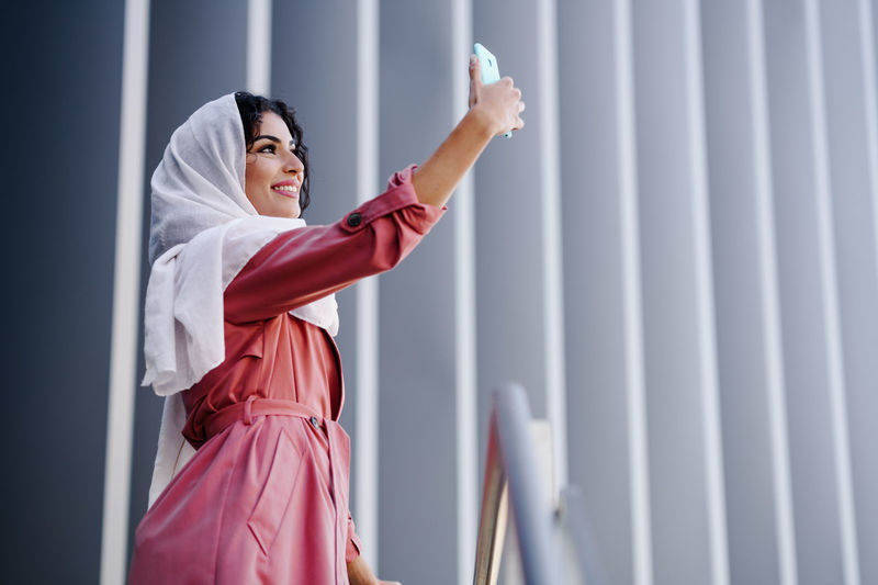 Woman taking selfie while standing against wall