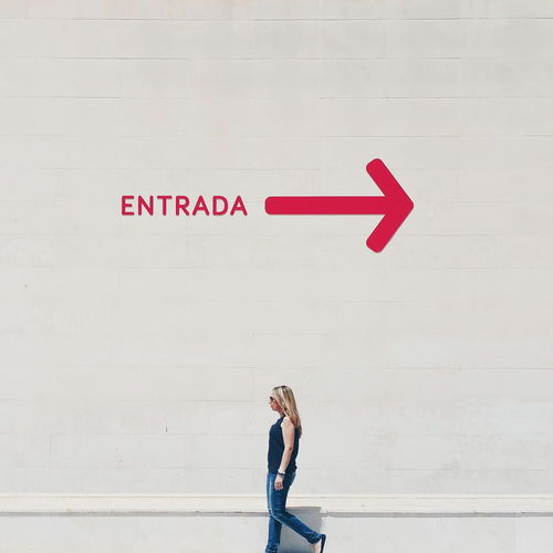 Profile View Of Woman Walking By Wall With Entrance Sign And Arrow Symbol