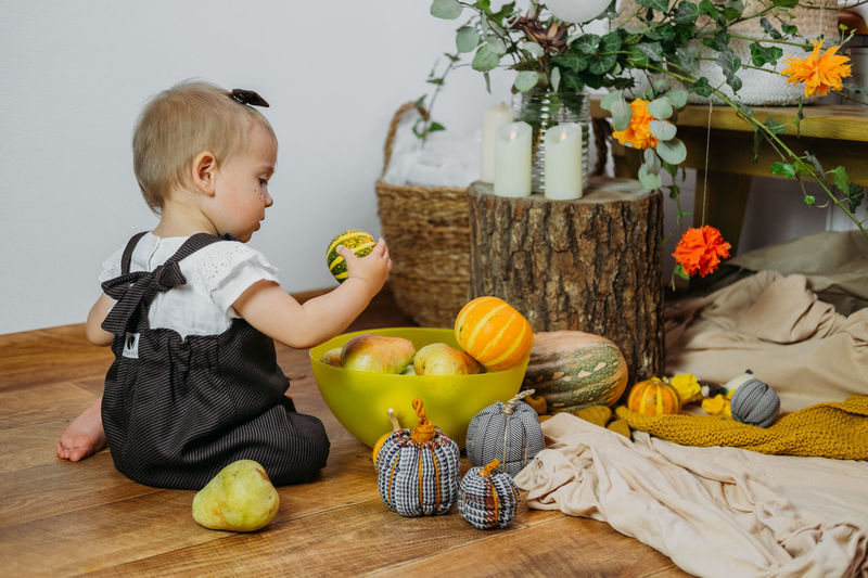 Full length of cute baby holding fruits while sitting at home