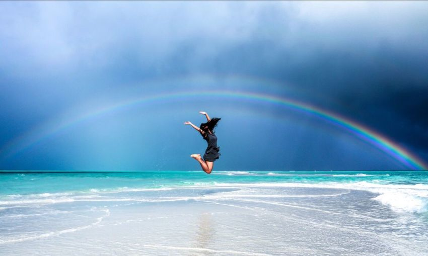 Mature Woman With Arms Raised Jumping At Beach Against Cloudy Sky