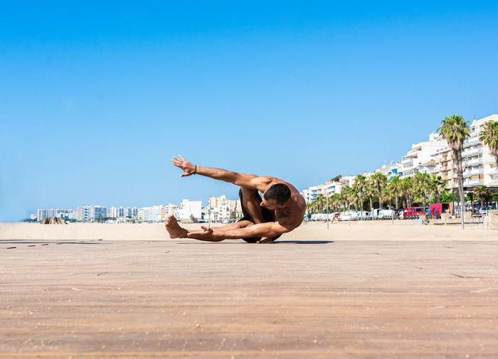Man with arms raised on beach against clear blue sky