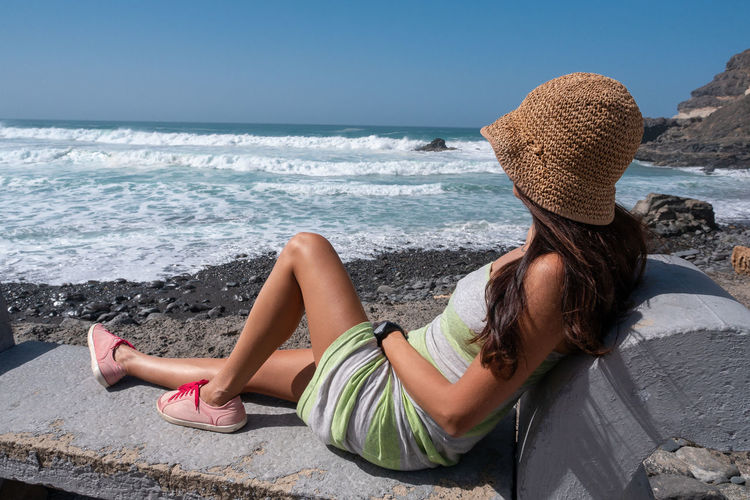 Sea Water One Person Real People Leisure Activity Beach Land Lifestyles Women Relaxation Sitting Beauty In Nature Young Women Hat Adult Nature Clothing Lying Down Hair Horizon Over Water Outdoors Hairstyle
