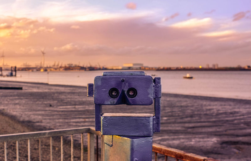 Close-up of binoculars at beach during sunset