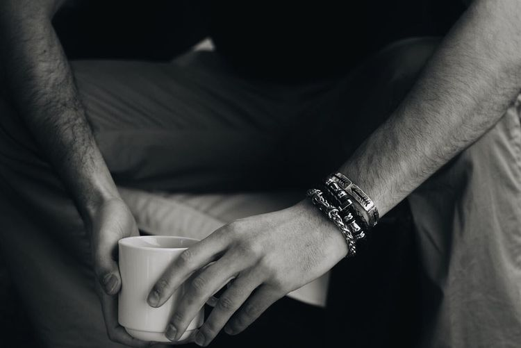 Midsection Of Man Holding Coffee Cup At Home