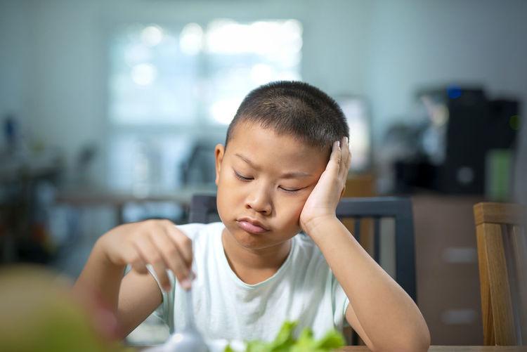 Close-up of sad boy eating food at home