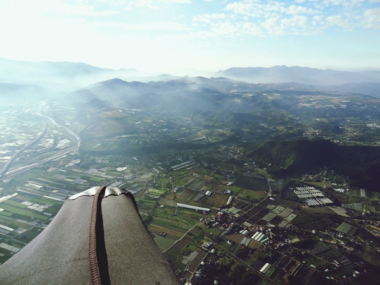Cropped image of airplane wing flying over landscape
