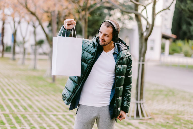 Mid adult man holding bag looking away while standing outdoors