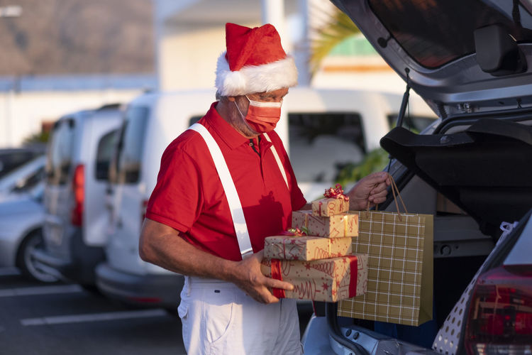 Senior man wearing mask holding christmas present standing by car trunk