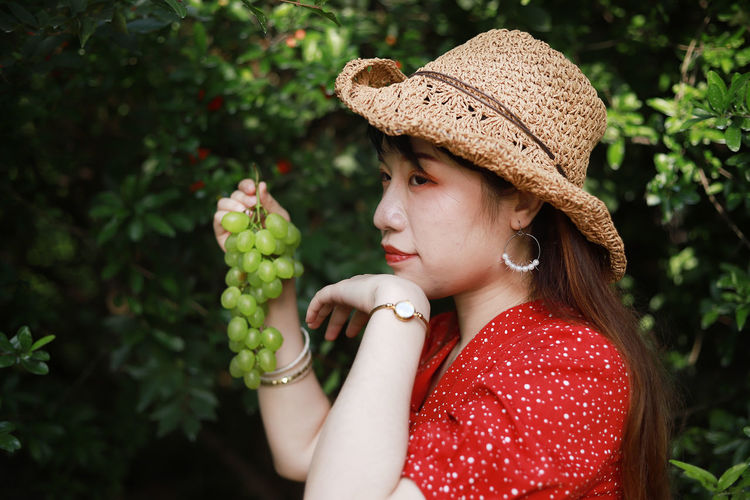 Young woman holding grapes while looking away against plants