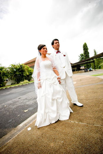 Bride and groom standing on footpath