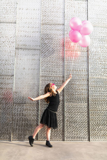 Full length of woman with pink balloons standing against wall