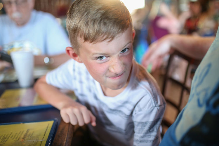 Boys Child Childhood Real People Smiling Happiness Indoors  Sitting Looking At Camera Innocence Silly Face Silly Faces  Restaurant Summer Summertime Dinner Time Family Dinner Family Time Boy Childhood Memories Silly Expression Focus On Foreground Blurry Background Blurred Background