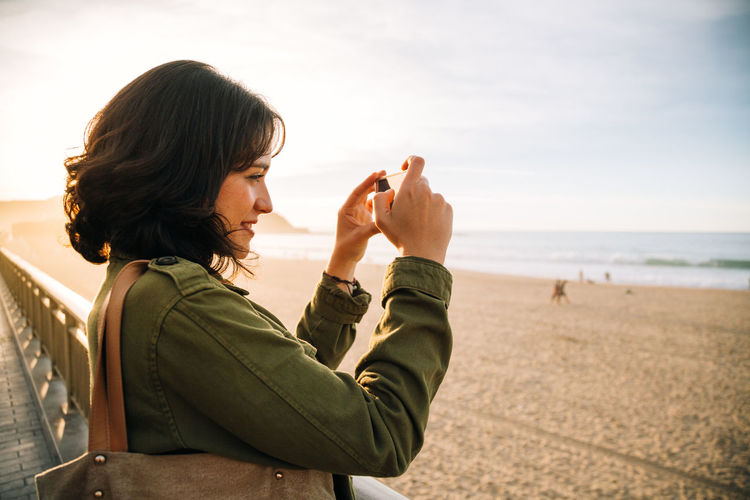 One Person Real People Beach Land Sea Leisure Activity Sky Lifestyles Adult Headshot Young Adult Side View Focus On Foreground Young Women Standing Women Portrait Outdoors Hairstyle Horizon Over Water Photographer Smart Phone Landscape Photography Tourist