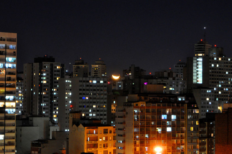Illuminated buildings against clear sky at night
