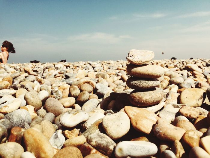 Stack of pebbles on beach against sky