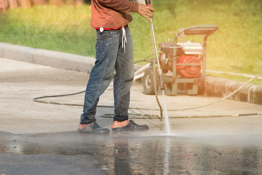High pressure deep cleaning. Worker cleaning driveway with gasoline high pressure washer ,sunlight background. Construction Site Driveway Gasoline High Pressure Cleaner Sunlight Water Wet Worker