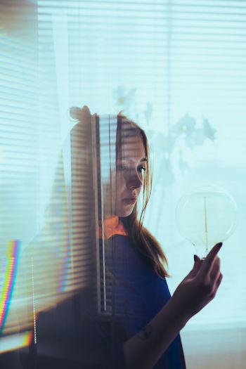 Portrait of woman holding glass window