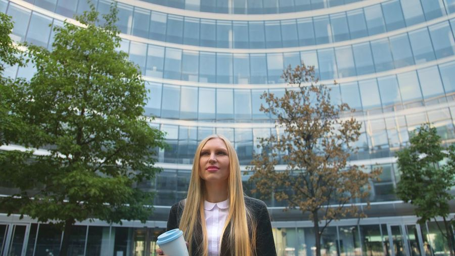 Businesswoman with blond hair standing outside office building