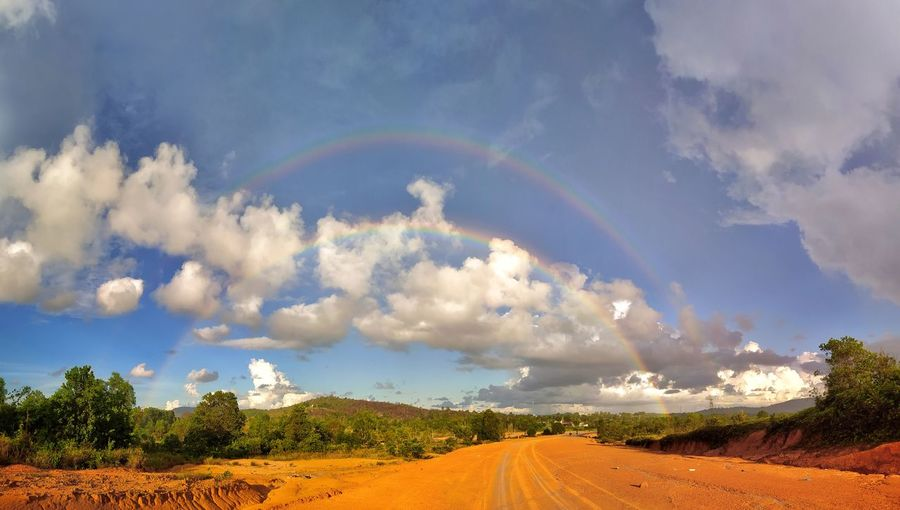 Scenic view of rainbow over road against sky