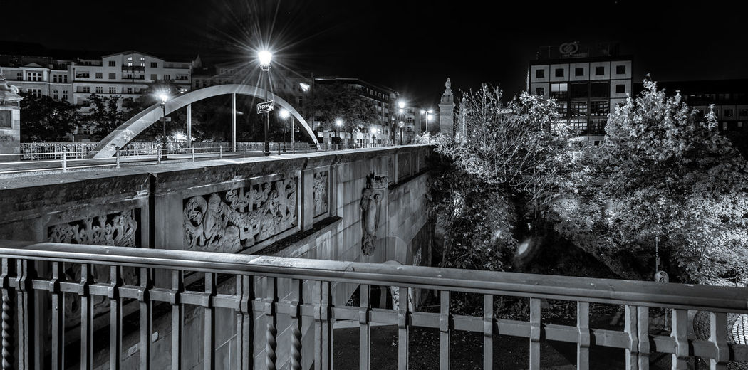 Bridge over canal in city at night