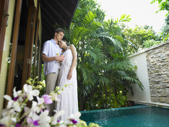 Couple Standing At Poolside