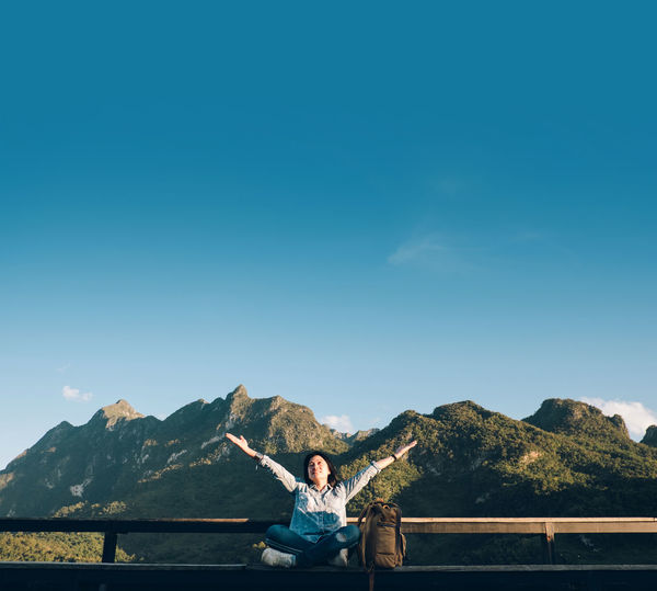 Smiling woman with arms raised sitting on railing with mountains in background