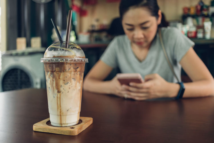 Midsection of man using mobile phone in cafe