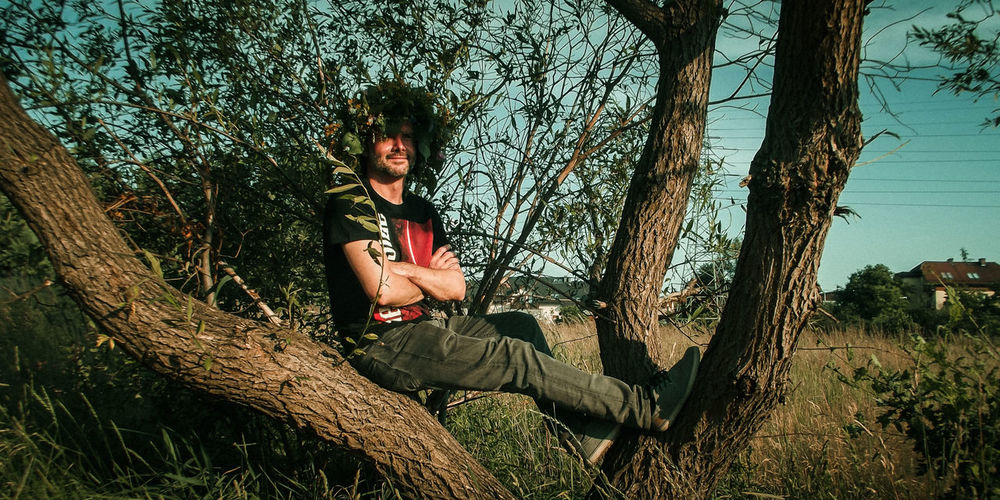 Portrait of smiling man with arms crossed sitting on tree in forest