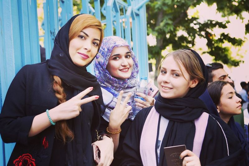 Portrait of smiling young women showing peace signs while standing outdoors