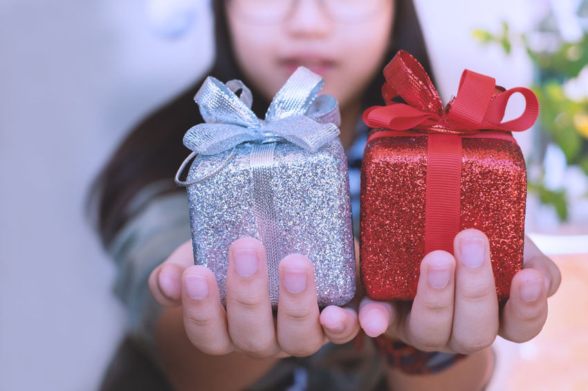 Gift One Person Holding Focus On Foreground Celebration Human Hand Ribbon Box Close-up Tied Bow Lifestyles Gift Box Glitter Reward Present Girl Kids Child Giving Handing Selective Focus Special Occasion Young Adult Christmas New Year