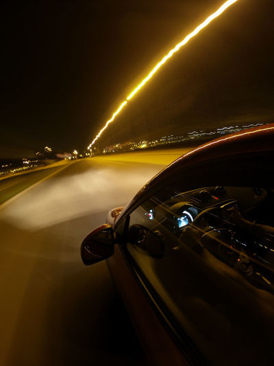 Cars on illuminated road against sky at night
