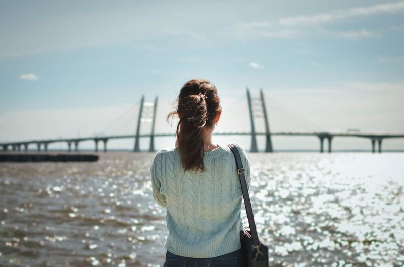 Rear view of woman standing on bridge against sky