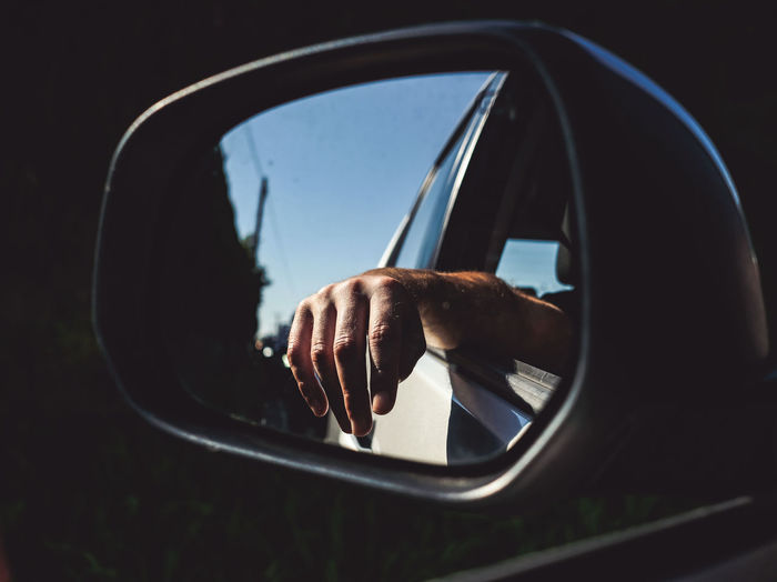 Close-up of hand in side-view mirror of car