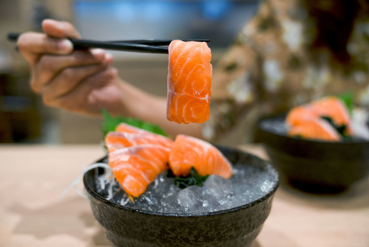 Midsection of person having sushi in restaurant